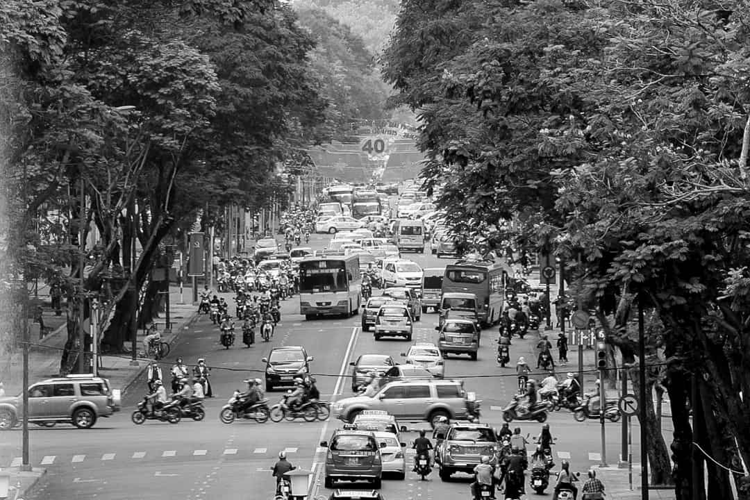 A black and white photograph of a street in Ho Chi Minh City, Vietnam, outside the presidential palace