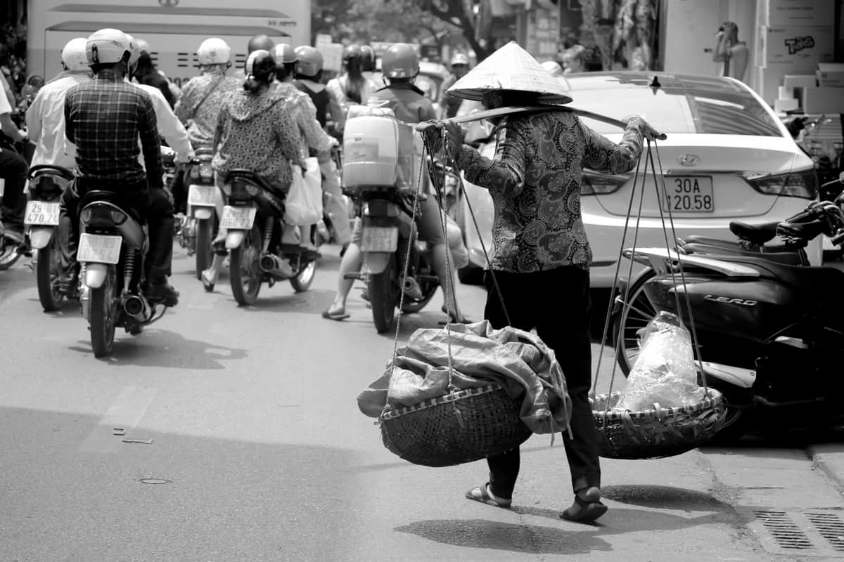 A black and white photo of a street vendor in Hanoi, Vietnam