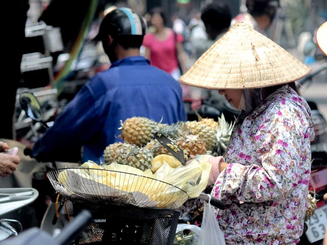 A woman buying fruit at a market in Hanoi, Vietnam