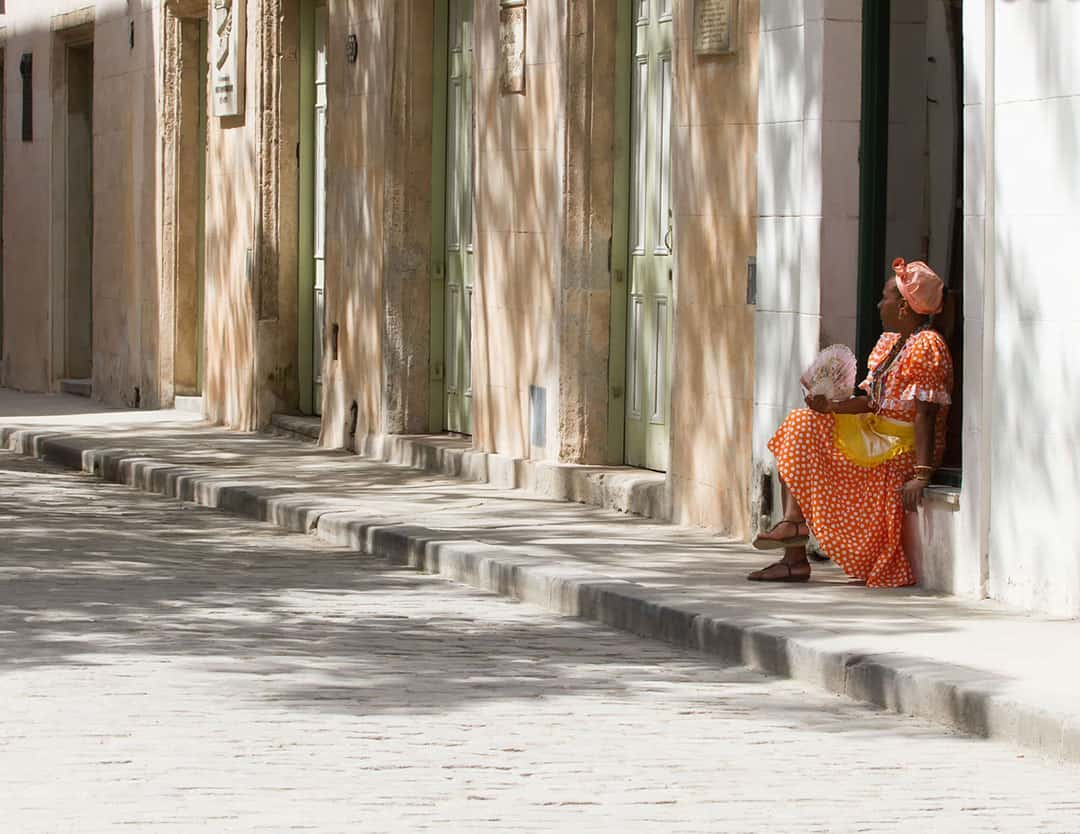 A Cuban woman sits on the side of the street wearing an orange rumba dress and holding a fan