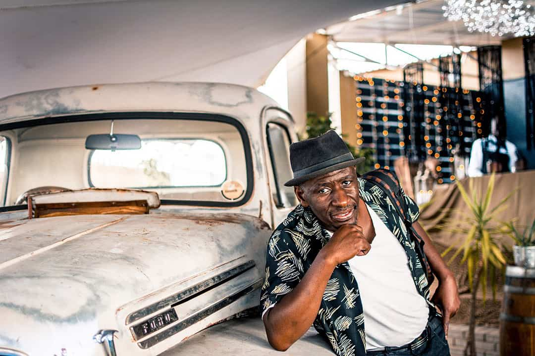 A Cuban man leaning on an old car wearing a printed shirt and hat
