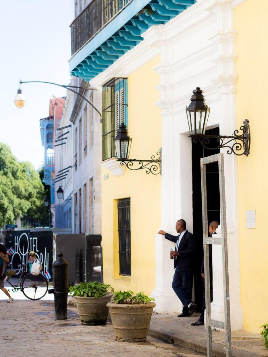 A man standing outside a yellow house in Havana Cuba
