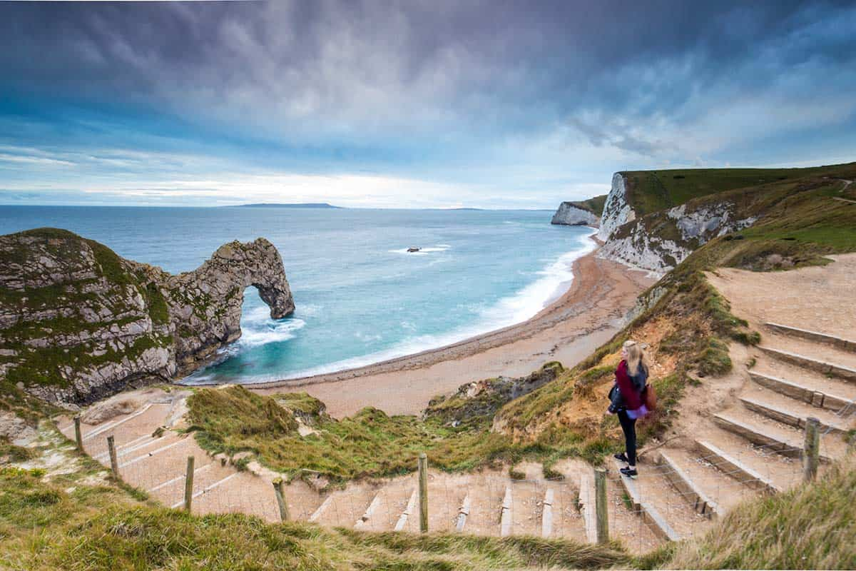 A woman standing on the path to Durdle Door on the Jurassic Coast in Dorset, England, UK
