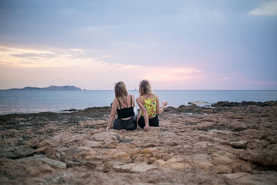 Two women watch the sunset on Playa Pinet beach in Ibiza