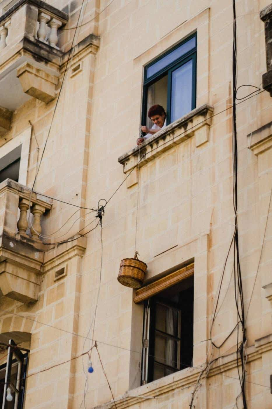 Maltese lady buying bread from her window in Valletta