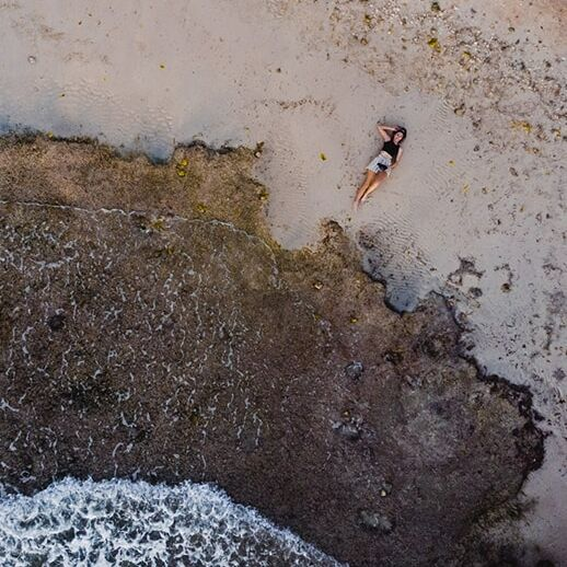 A drone shot of travel blogger Alajode lying on a beach in Cebu, the Philippines