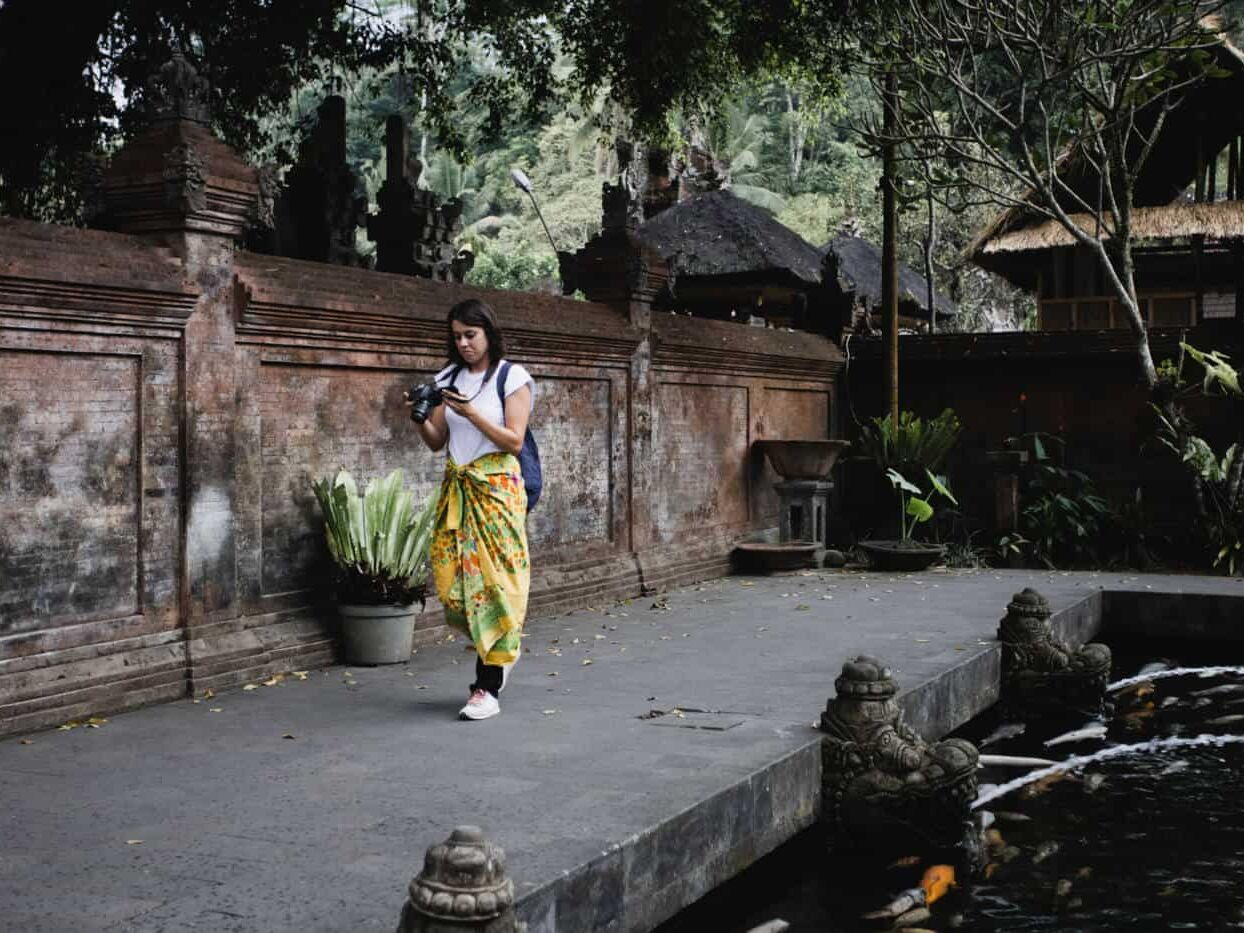 A woman in a yellow sarong at Tirta Empul Temple in Bali