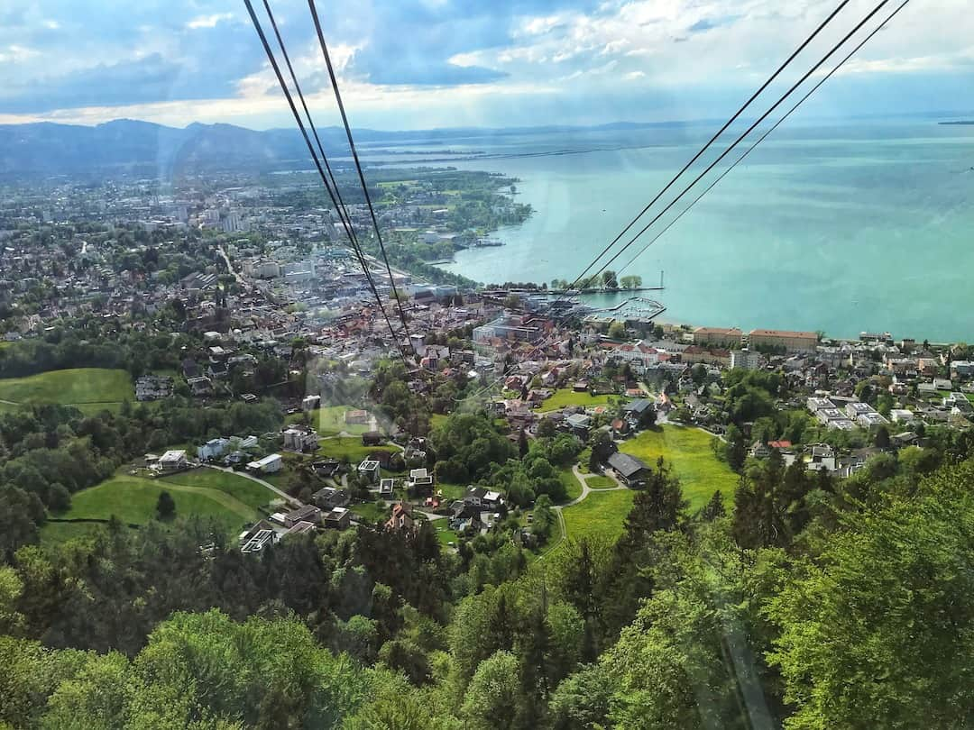 The Bregrenz Gondola and a view over Bregenz. There are trees in the foreground and the sea is behind the city