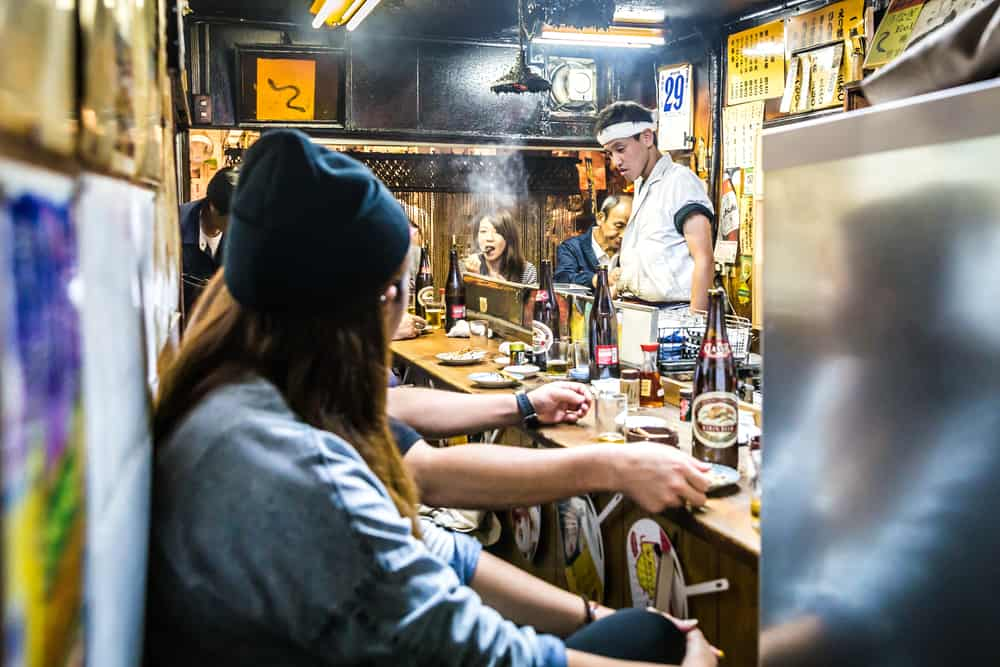 Several people sat at a bar eating and drinking while a chef cooks foods