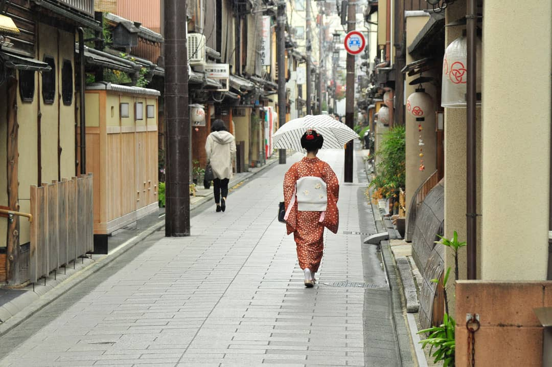 A geisha walking down the street in the Gion district of Kyoto