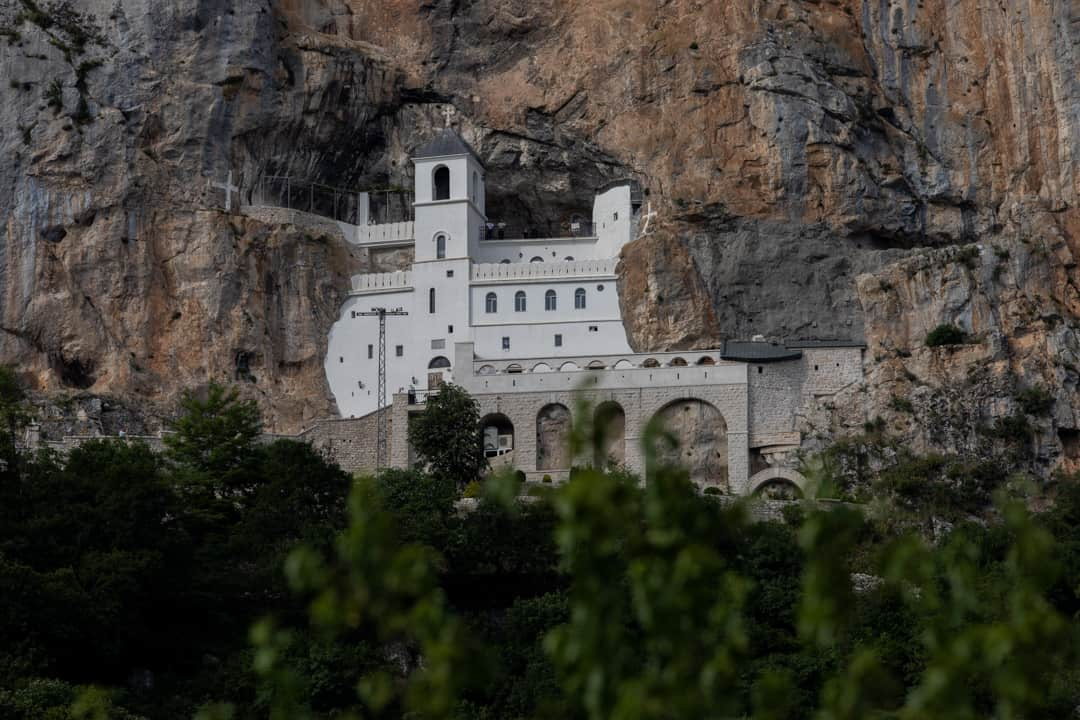 A white monastery embedded in a cliff edge