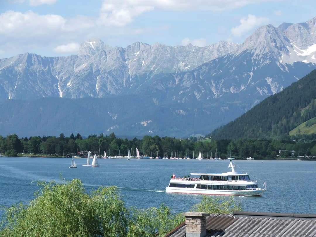 A yacht on the lake in Zell am See with mountains behind it