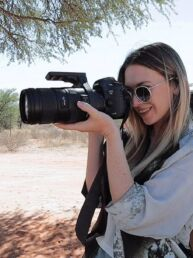 Woman taking photos on a telephoto lens and Canon DSLR camera on safari