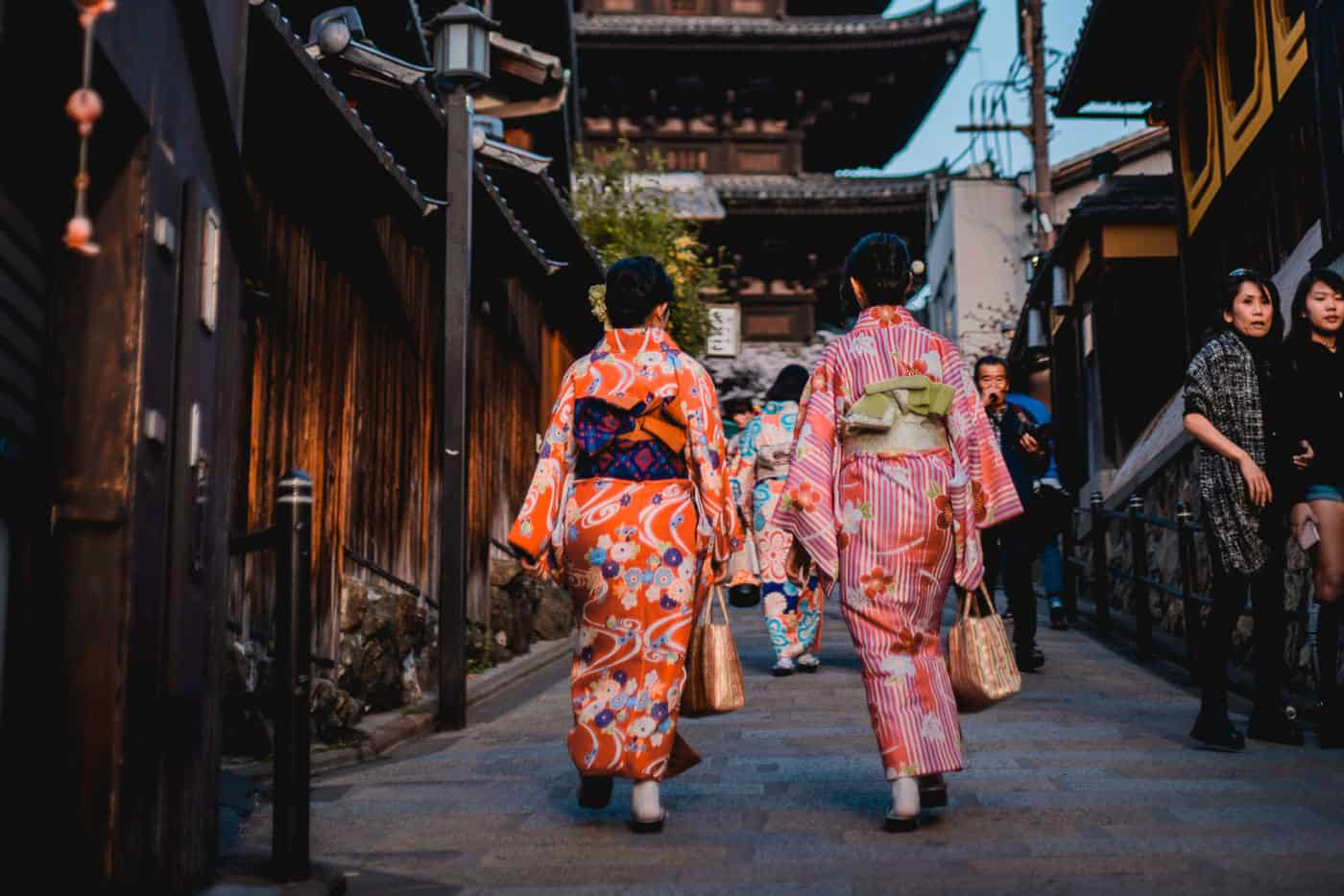 Two women dressed in Japanese kimonos walking down a street in Gion Kyoto