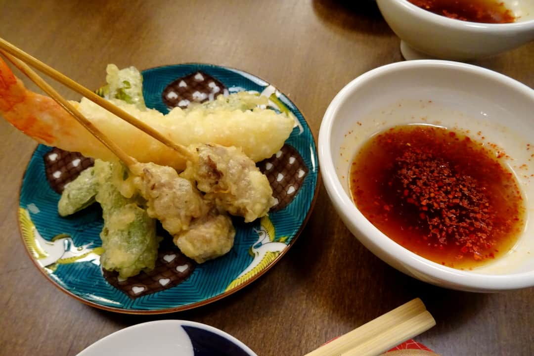 Shrimp tempura next to a bowl of dip on a food tour of kyoto