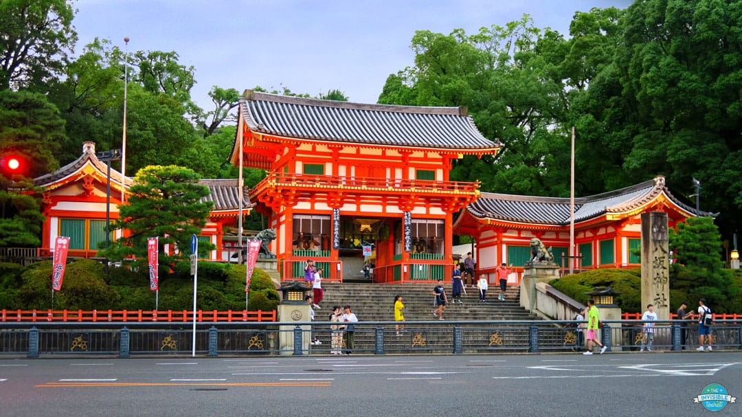 A bright red shrine with people standing outside