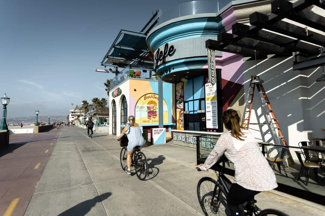 Two women ride bikes outside brightly coloured shops front in Mission Beach in San Diego California USA