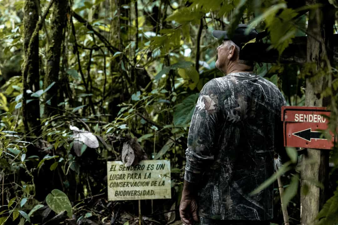 A guide standing next to a sign about respecting nature in the Barbas Bremen Reserve in Colombia