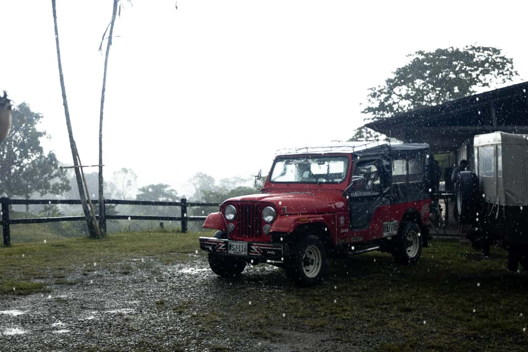 A red jeep sits in a rainstorm in Filandia Colombia