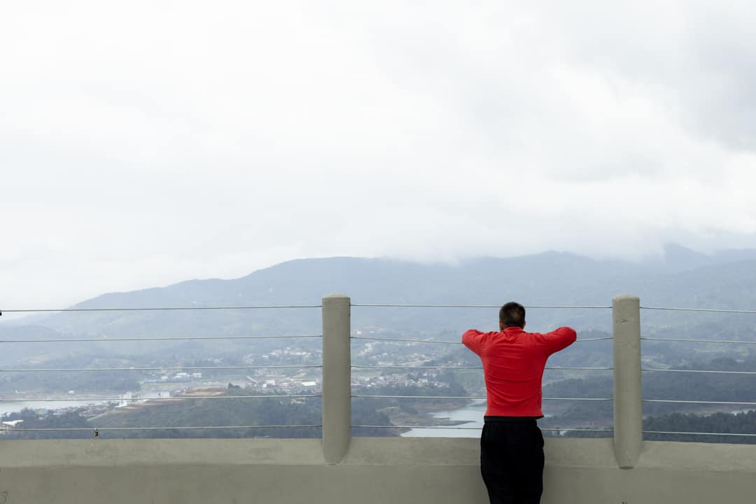 A man looking at the view from Piedra el penol in Colombia