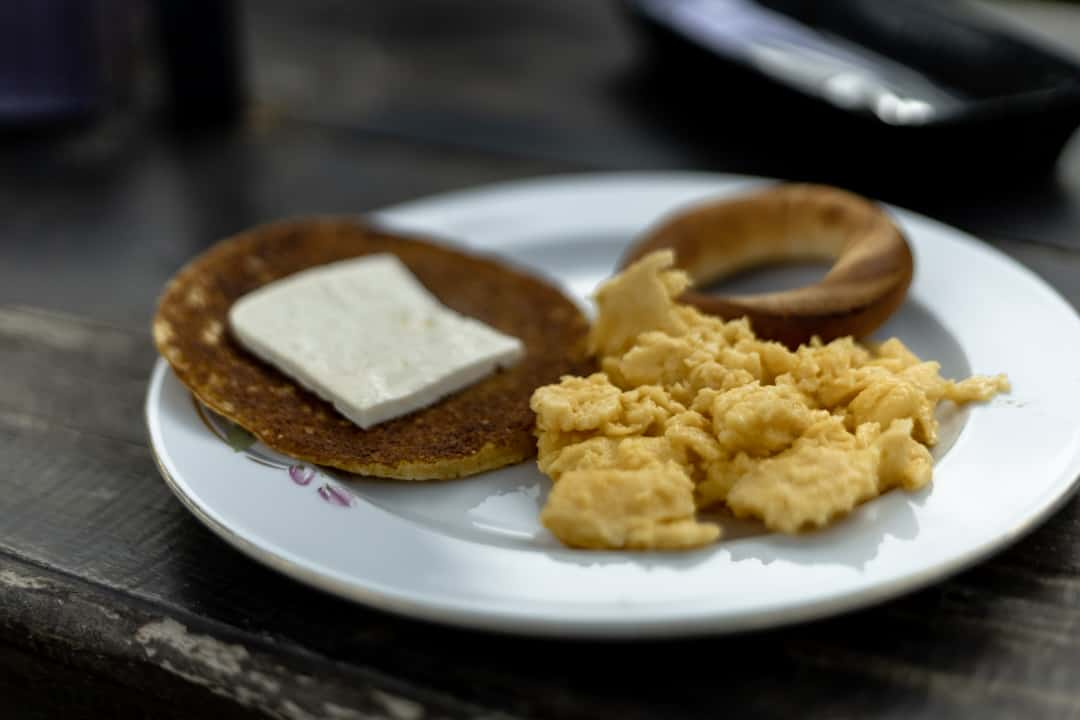 A Colombian breakfast consisting of arepas de choclo, scrmabled eggs a pastry