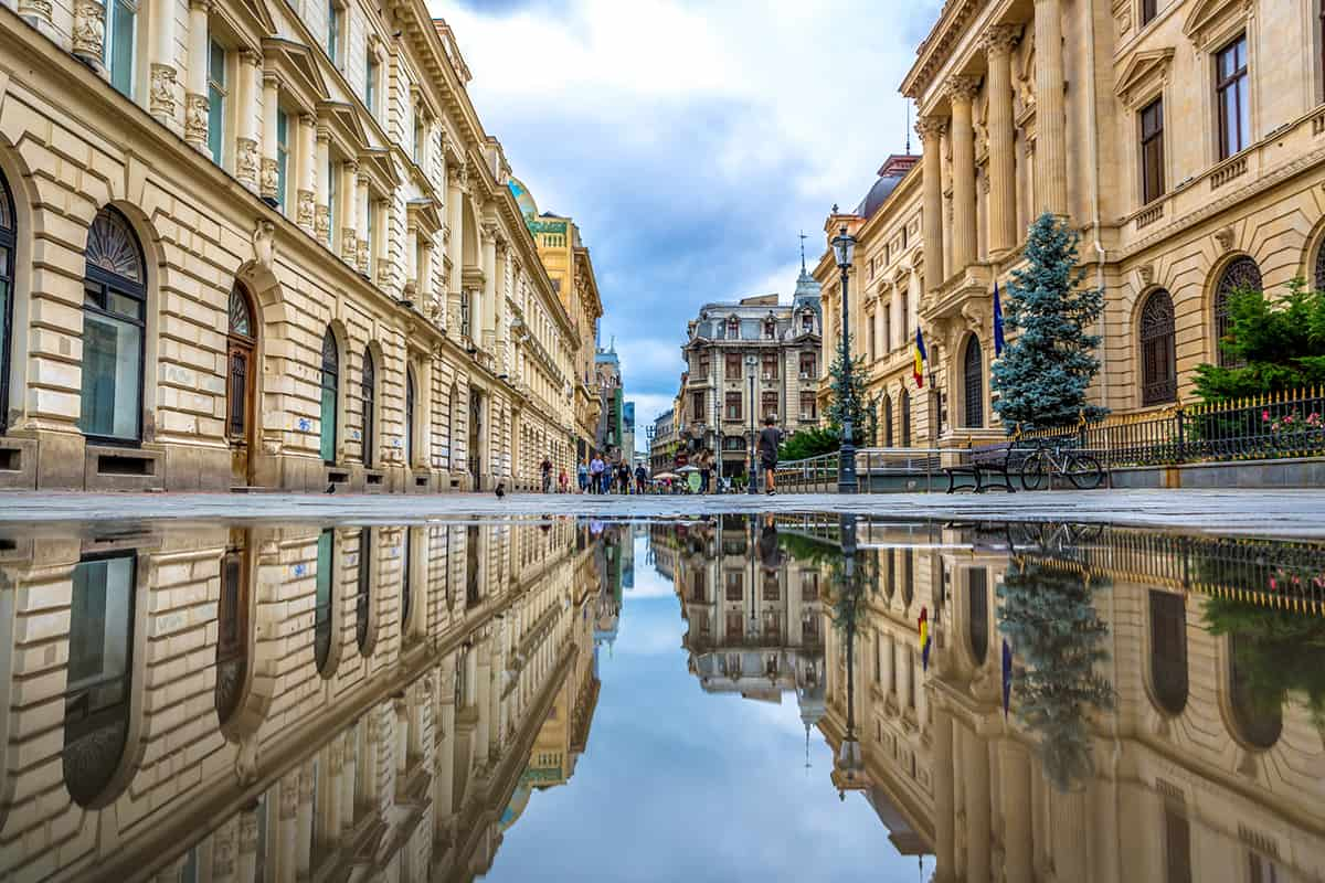 The old town of Bucharest seen through a water reflection with people in the background in Romania